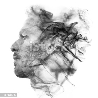 istock Double exposure portrait of a sexy statuesque man with dark features blending into a curtain of smoke 1157821717