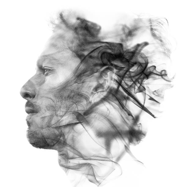 Double exposure portrait of a sexy statuesque man with dark features blending into a curtain of smoke stock photo