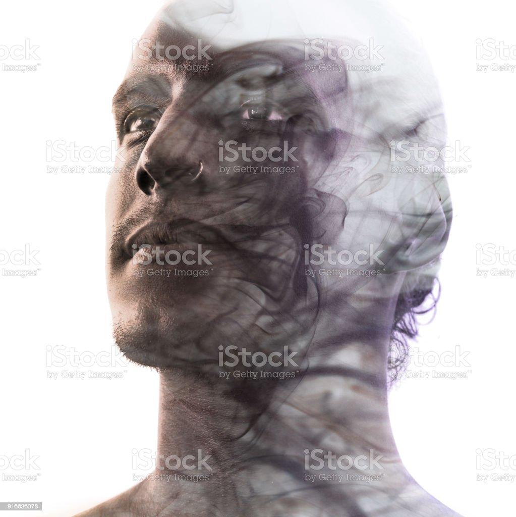 Double exposure portrait of a statuesque man with dark features blending into a curtain of smoke stock photo