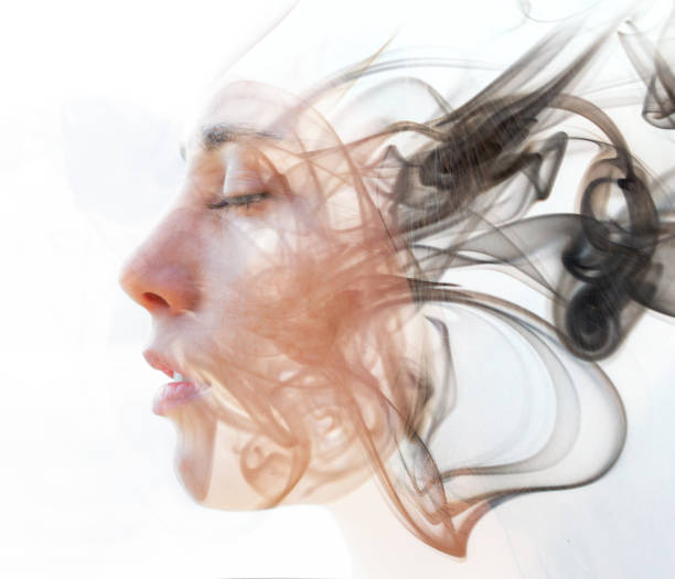 Double exposure portrait of a young fair-skinned woman and a smoky texture dissolving into her facial features stock photo
