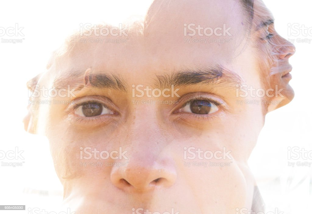 Double exposure portrait of a young fit man, pensive yet relaxed blended seamlessly with a profile portrait of himself stock photo