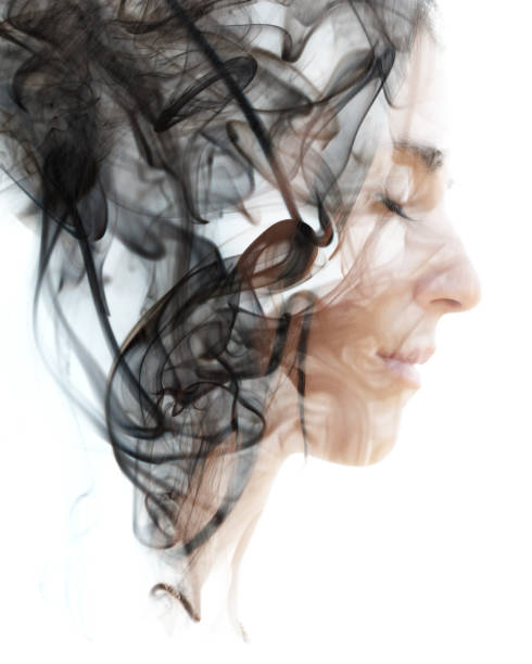 Double exposure portrait of a young woman and a smoky texture dissolving into her hair and face stock photo