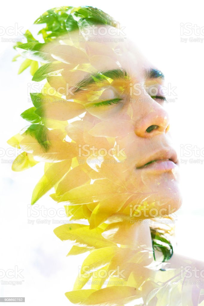 Double exposure, profile of a young sexy man blended with lush tropical leaves shows the perfect beauty of nature's creation stock photo