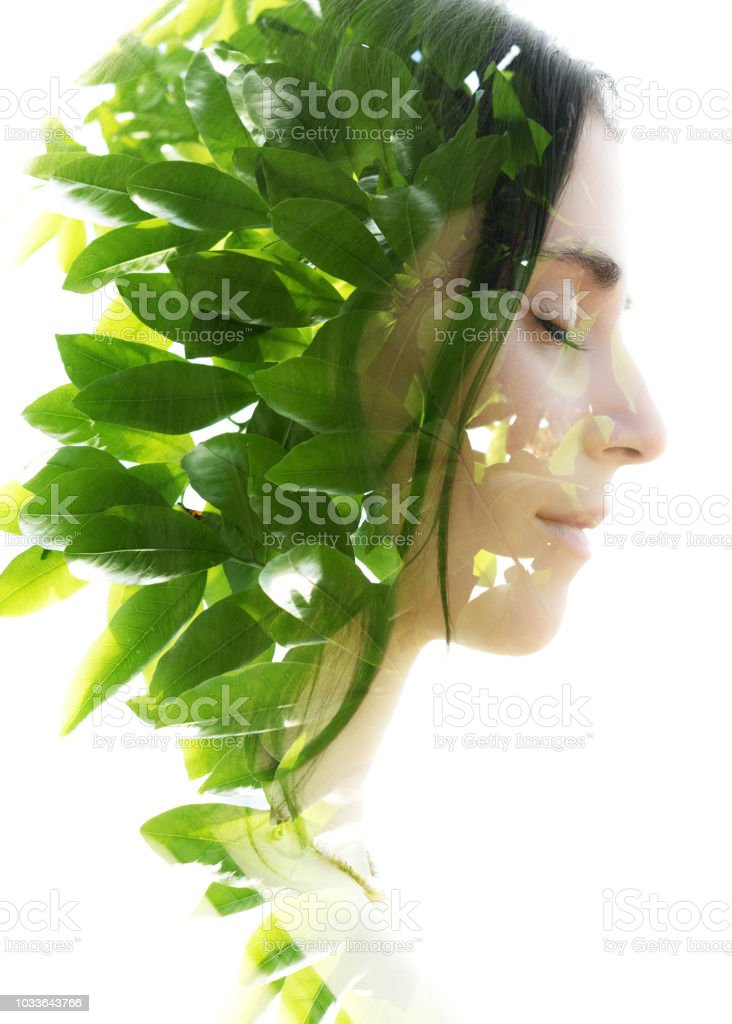 Double exposure profile portrait of a naturally beautiful woman with closed eyes and bright green tropical leaves stock photo
