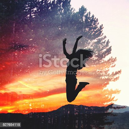 Double exposure vintage toned image, silhouette of a woman jumping against the sky just as the sun has set behind the mountain range.
