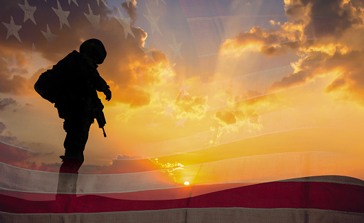 istock Double exposure Silhouette of Soldier on the United States flag in sunset for Veterans Day is an official USA public holiday background,copy space. 1053001126