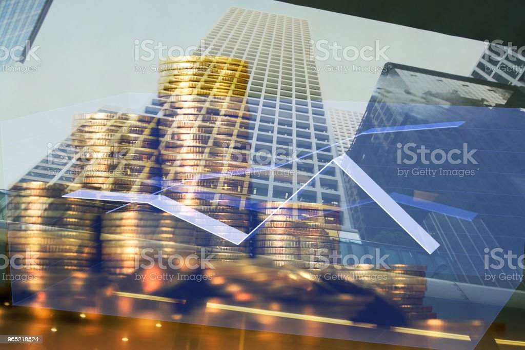 Double exposure Stack of coin with financial graph over city and office building background, business and financial concept. royalty-free stock photo