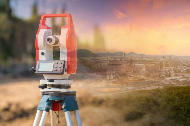 Double exposure surveyor equipment theodolite outdoors with panorama view of oil and gas refinery plant stock photo