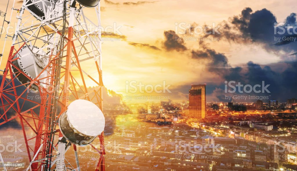 Double exposure telecommunication towers with TV antennas and satellite dish in sunset, with city background stock photo