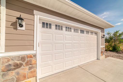 Double garage of modern home on sunny, clear day. A double garage and driveway of a modern home on a sunny, clear day.