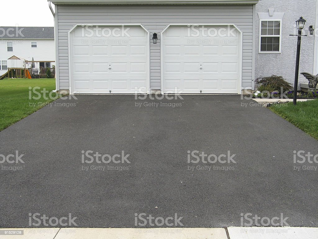A double garage with white doors at the end of a driveway stock photo