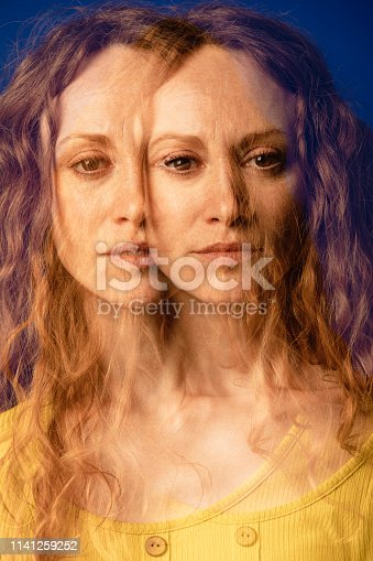 Multiple exposure portrait of a woman standing in front of a blue coloured background. In both exposures she is looking at the camera but her expressions slightly differ.