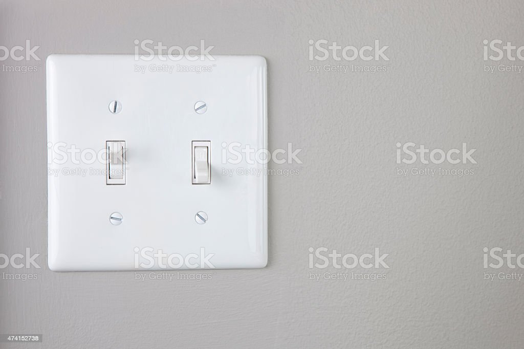 Double light switch on a painted gray wall. Copy Space stock photo