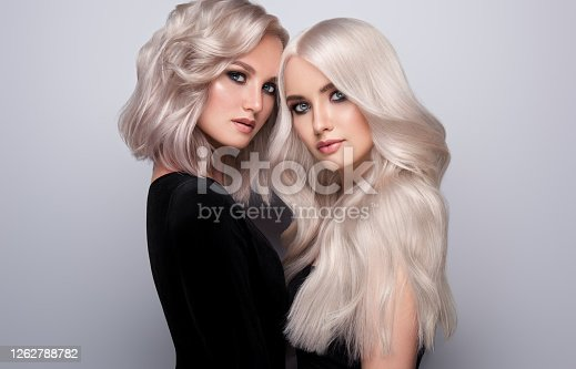 Two examples of blond hairstyle on the heads of nicely looking women. Double portrait of blondes with different length of hair.  Coloration in blond. Stylish blond haire. Beauty, elegance, art of hairstyling.