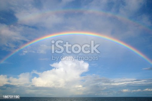 A double rainbow arc with large cumulus cloud over the sea