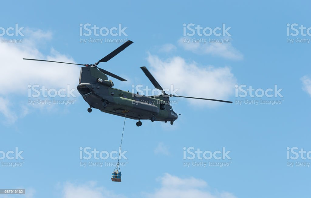 Double rotor, heavy airlift, military helicopter, in flight, carrying cargo. stock photo