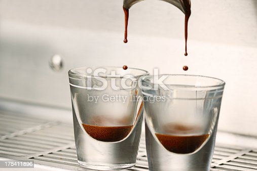 Close up action photo of a double shot espresso extraction into shot glasses.
