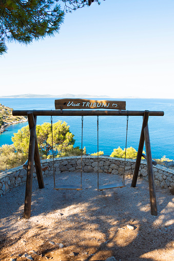 Tribunj, Croatia - August 6, 2021: Viewpoint terrace on a promenade on the hill by the sea with the double swing and a beautiful view point