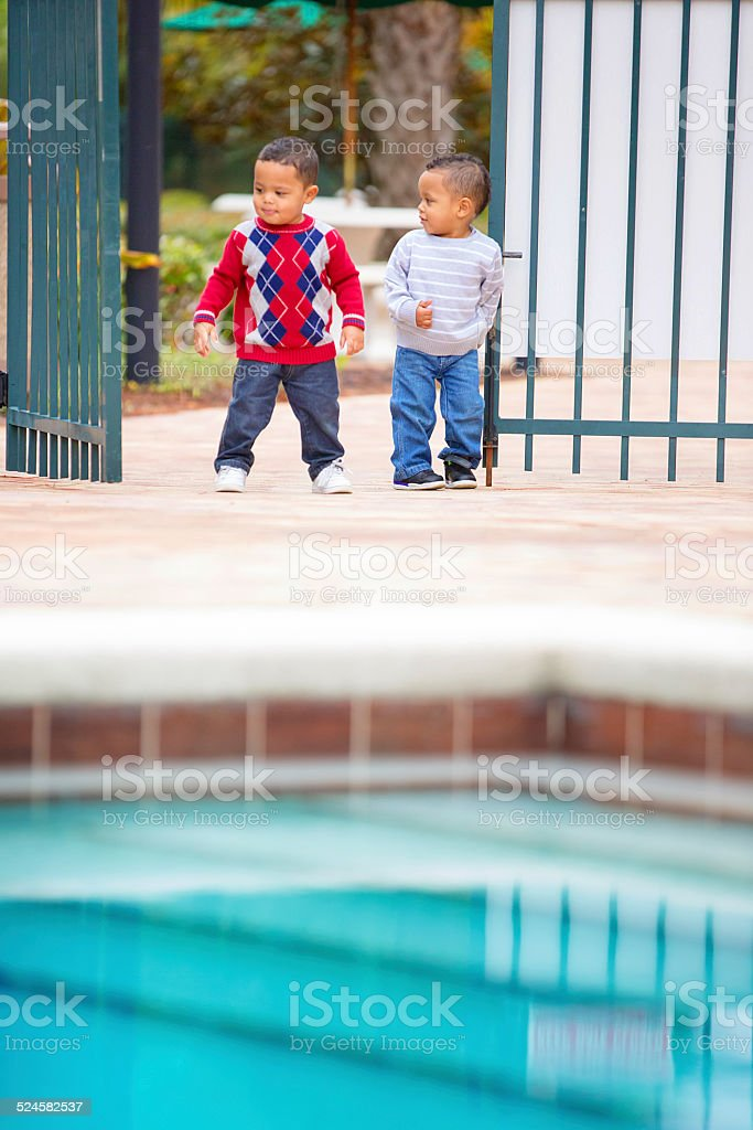 Double trouble! Twin boys try to get into locked pool stock photo