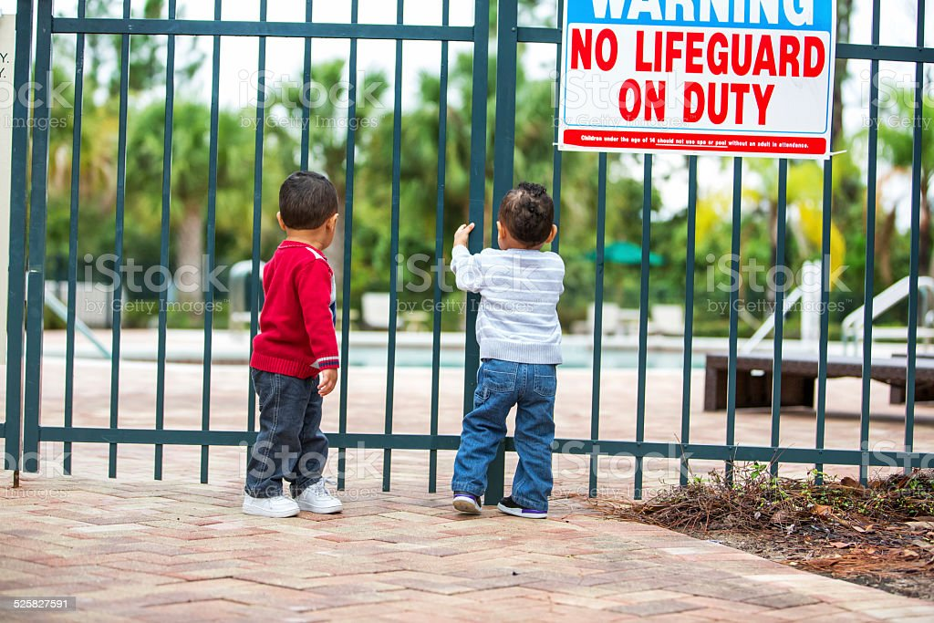 Double trouble. Twin boys try to get into locked pool stock photo