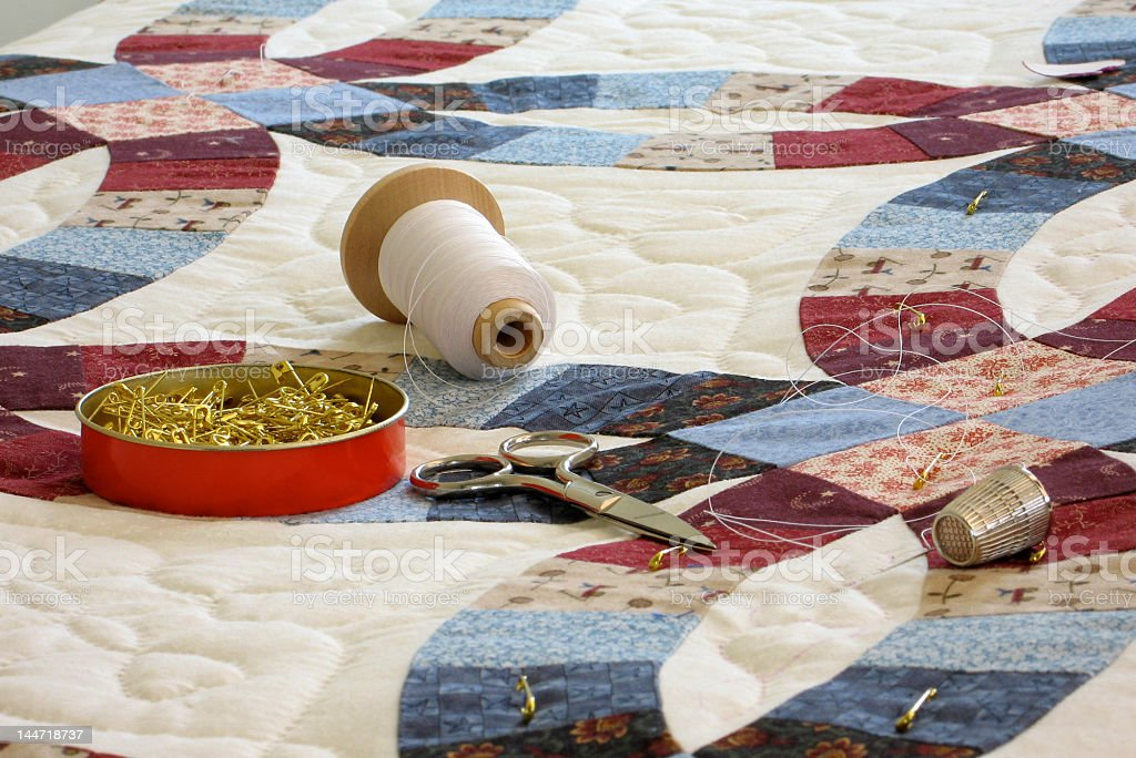 Double wedding ring patterned quilt with quilting tools stock photo