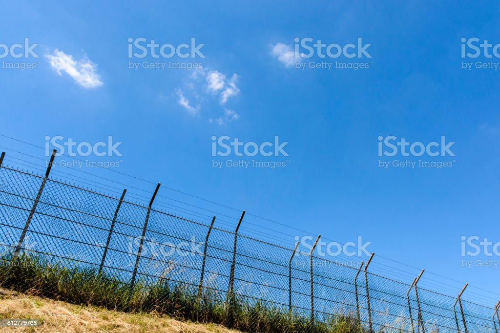 A double wire fence with barbed wire on top of a bank. stock photo