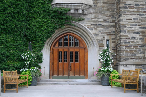 double wooden front door with leaded glass and ivy covered stone wall of gothic style college building double wooden front door with leaded glass and ivy covered stone wall of gothic style college building ivy league university stock pictures, royalty-free photos & images