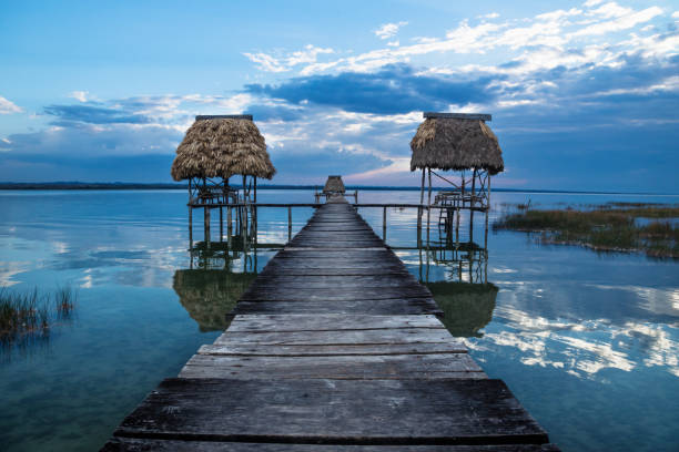 Double wooden old dock during sunset at lake Itza, El Remate, Peten, Guatemala stock photo