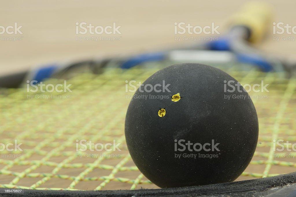 Double yellow dot squash ball on a racket. stock photo