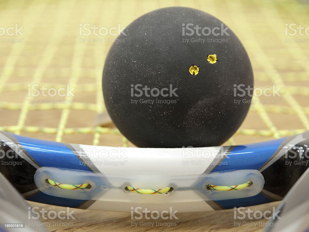 Double yellow dot squash ball on racket. royalty-free stock photo