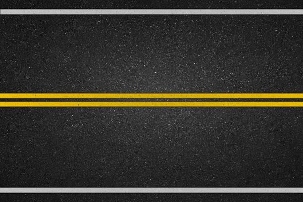 Doppie righe giallo su strada asfaltata - foto stock