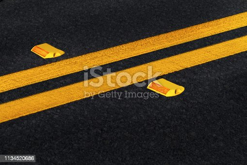 Double yellow lines on black asphalt road with reflectors