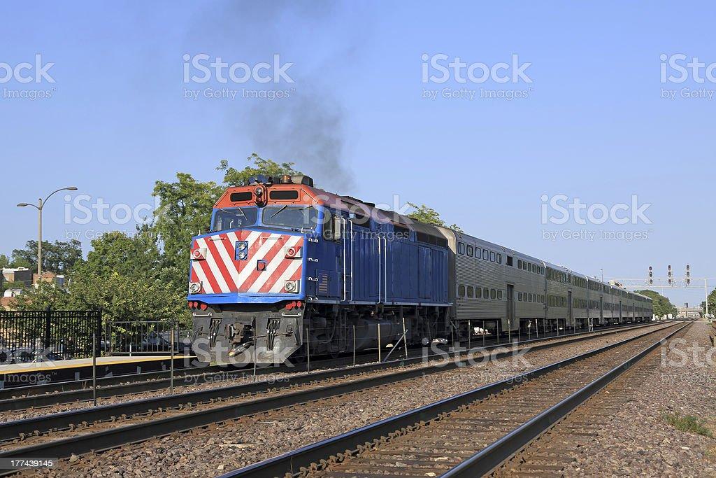 Double-decker commuter train approaching station stock photo