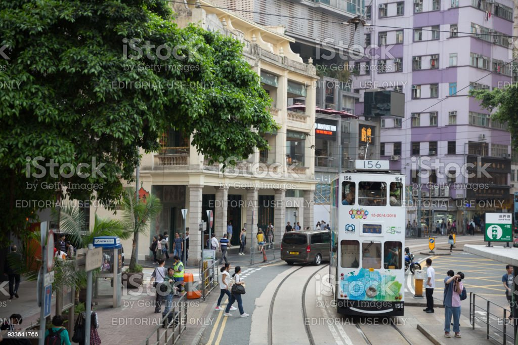 Double-decker Trams in Hong Kong Hong Kong, Hong Kong - March 16, 2018: People walk past the road in Wan Chai. Double-decker trams move past Wan Chai in Hong Kong. Many Passengers are inside the double-decker tram. Hong Kong has the world's largest operating fleet of double-decker trams. Arrival Stock Photo