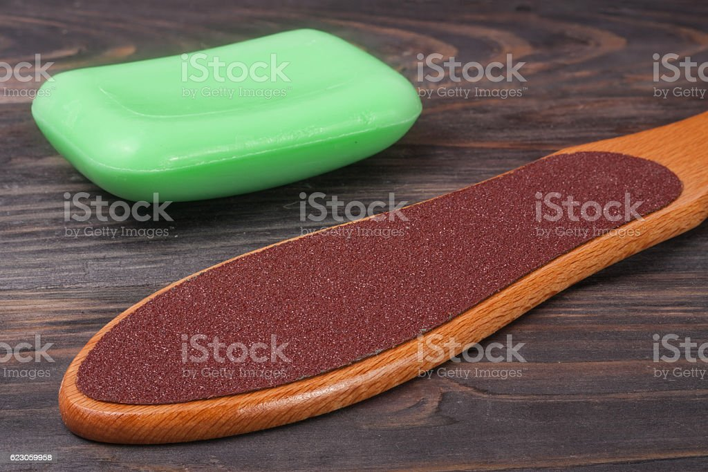 double-sided grater for feet with soap on a wooden stock photo