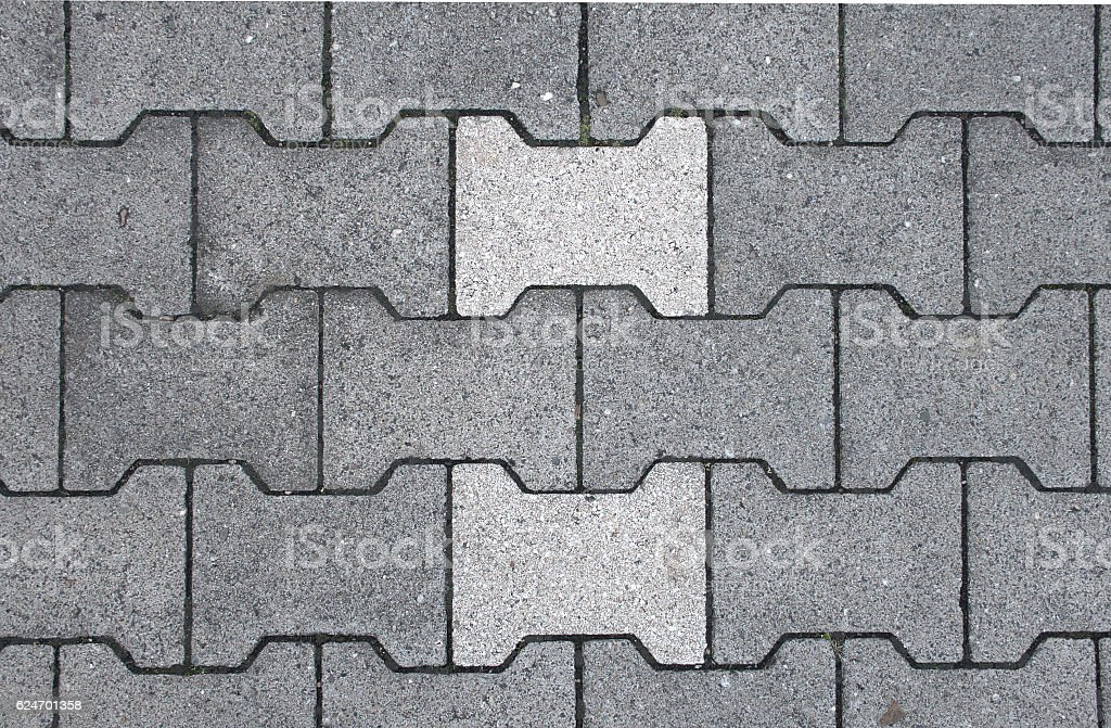 Double-T concrete stones with lighter stones forming a pattern texture stock photo