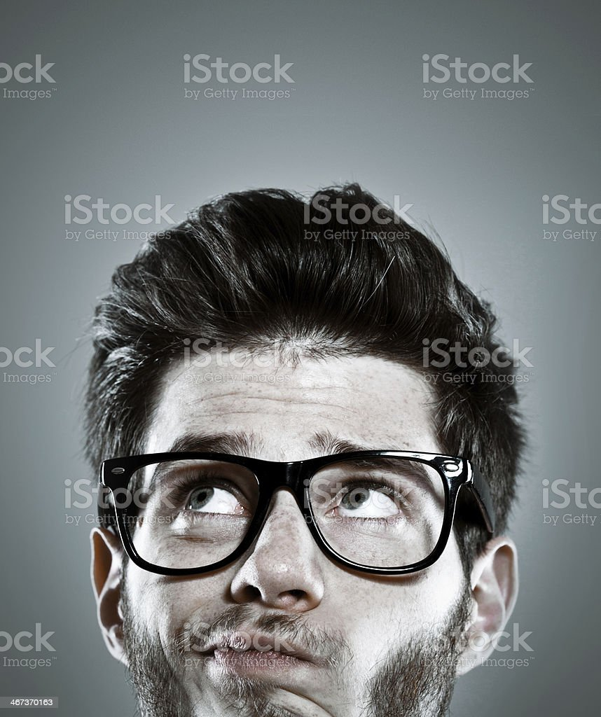 Doubt Close up of young man face with doubtful expression. Studio shot, grey background. 20-29 Years Stock Photo