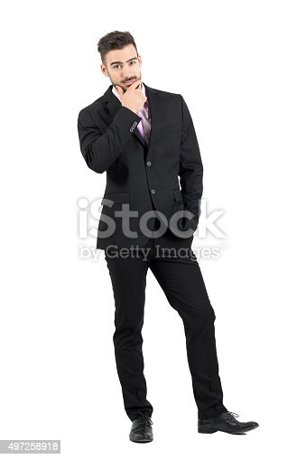 498403166 istock photo Doubtful businessman with hand on his chin looking at camera 497258918