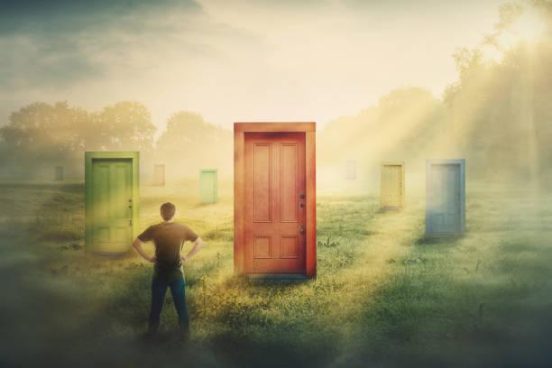 多くの異なったドアの前で怪しい男は1つを選びます。困難な決定、生命、失敗または成功における重要性の選択の概念。未知の将来のキャリア開発への道 - 機会 ストックフォトと画像