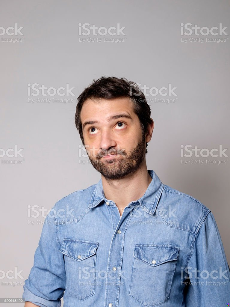 Doubtful man on gray background stock photo