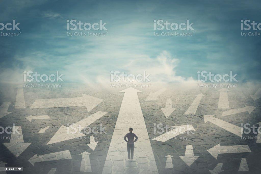 疑わしい人は、腰に手を、異なる方向の混乱を示す道路上の複数の矢印として方法を選択します。正しい経路、困難な意思決定の概念、混乱のシンボルを選択します。 - アイデアのロイヤリティフリーストックフォト