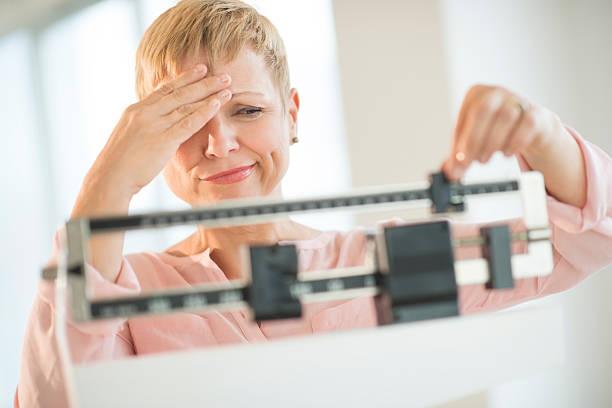 doubtful woman adjusting weight scale - lichaamsbewustzijn stockfoto's en -beelden