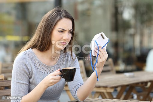 Doubtful young woman looking suspicious at protective face mask on a coffee shop terrace