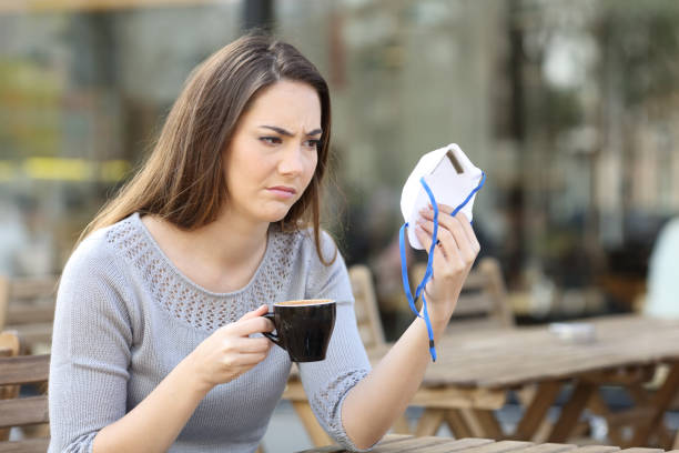 Doubtful woman looking at protective mask on a coffee shop stock photo
