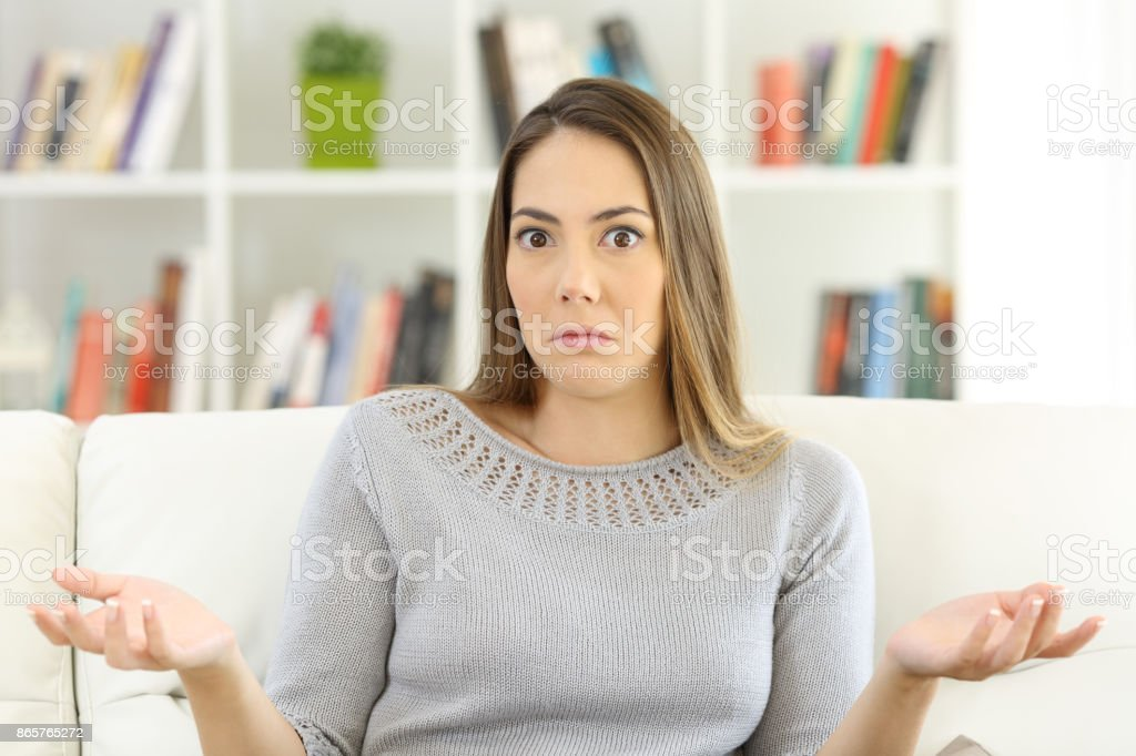 Doubtful woman shrugging shoulders at home stock photo
