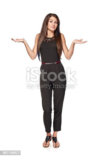 Doubtful woman standing in full length with two opened hand palms shrugging shoulders, isolated on white background