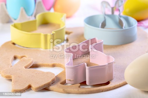 Dough and cutters for making Easter cookies and Easter eggs on a white wooden table. Concept of festive Easter baking.