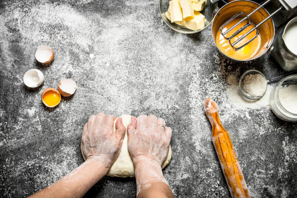 dough background. woman kneads dough with various ingredients on the table. - impastare foto e immagini stock