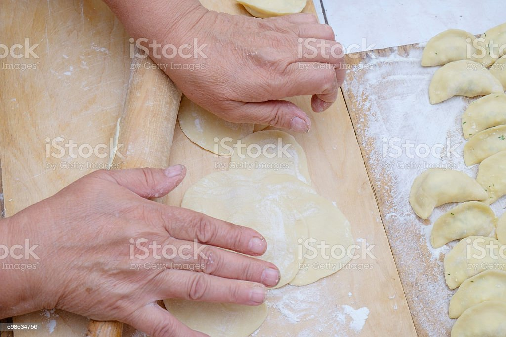 Dough being flattened on a wooden wooden board photo libre de droits
