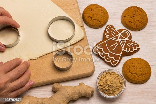 istock Dough for baking ginger cookies on a cutting board, cookie-cutter, hands cut out cookies 1198792671